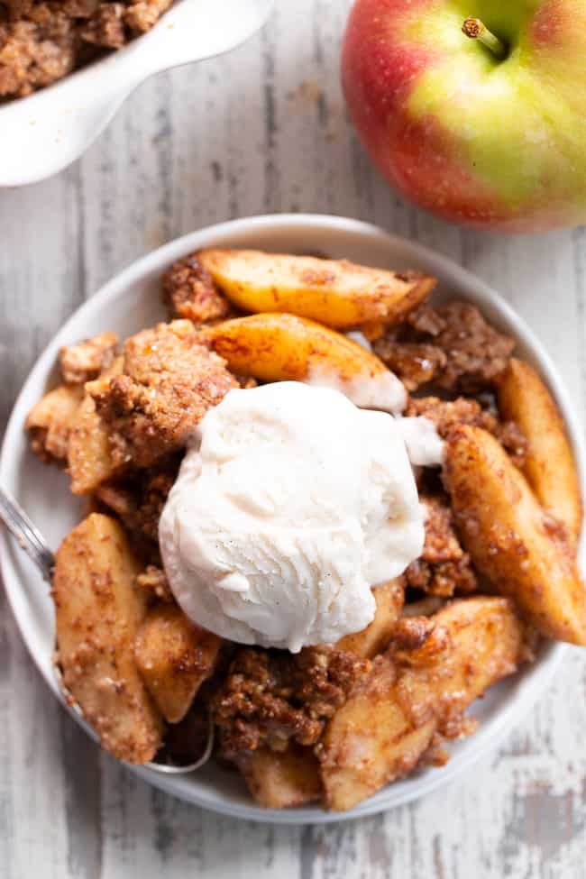 apple crisp in a white bowl with vanilla ice cream on top