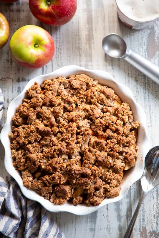 apple crisp in a baking dish alongside fresh apples and an ice cream scoop