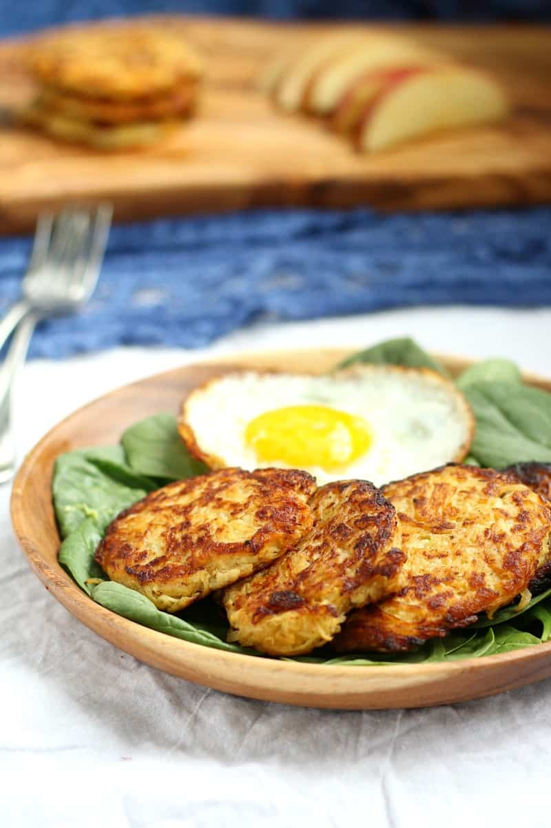 spaghetti squash apple fritters and a fried egg over a bed of spinach in a bowl
