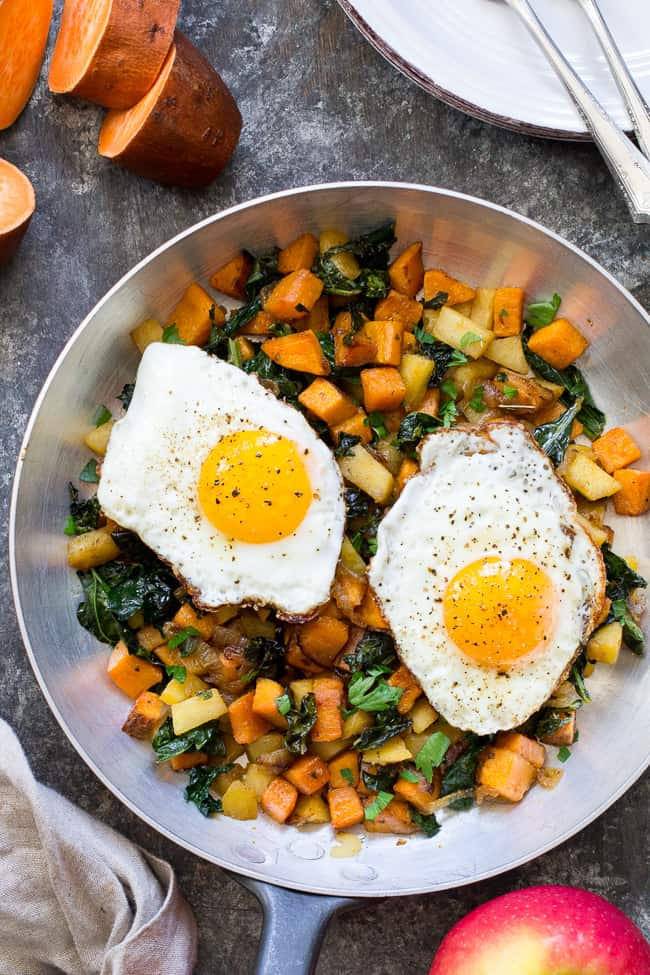 skillet of sweet potato hash with two fried eggs on top