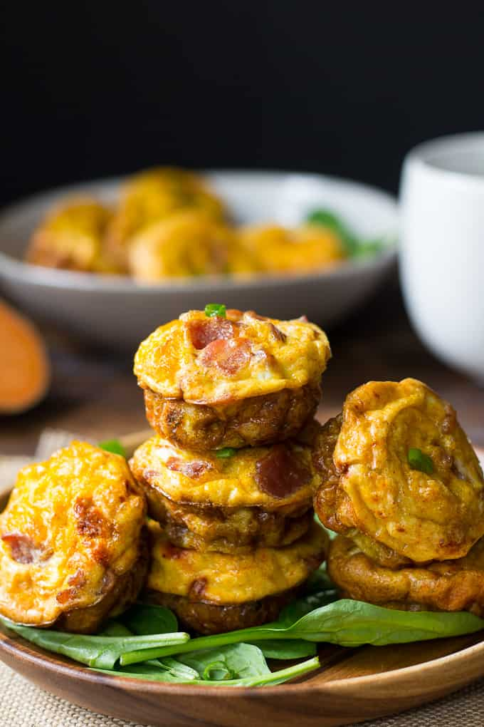 sweet potato bacon egg muffins stacked on a bed of greens