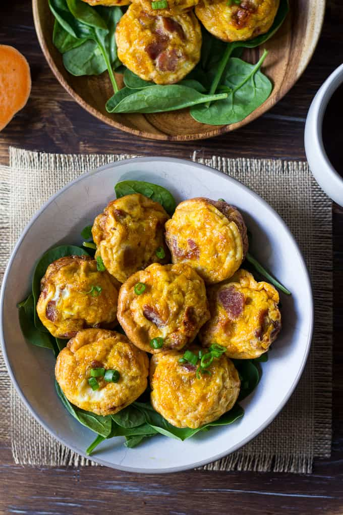 seven egg muffins on a bed of greens in a white bowl