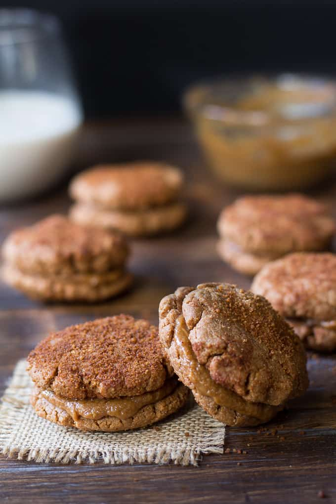 almond butter snickerdoodle sandwich cookies on a board with a glass of milk
