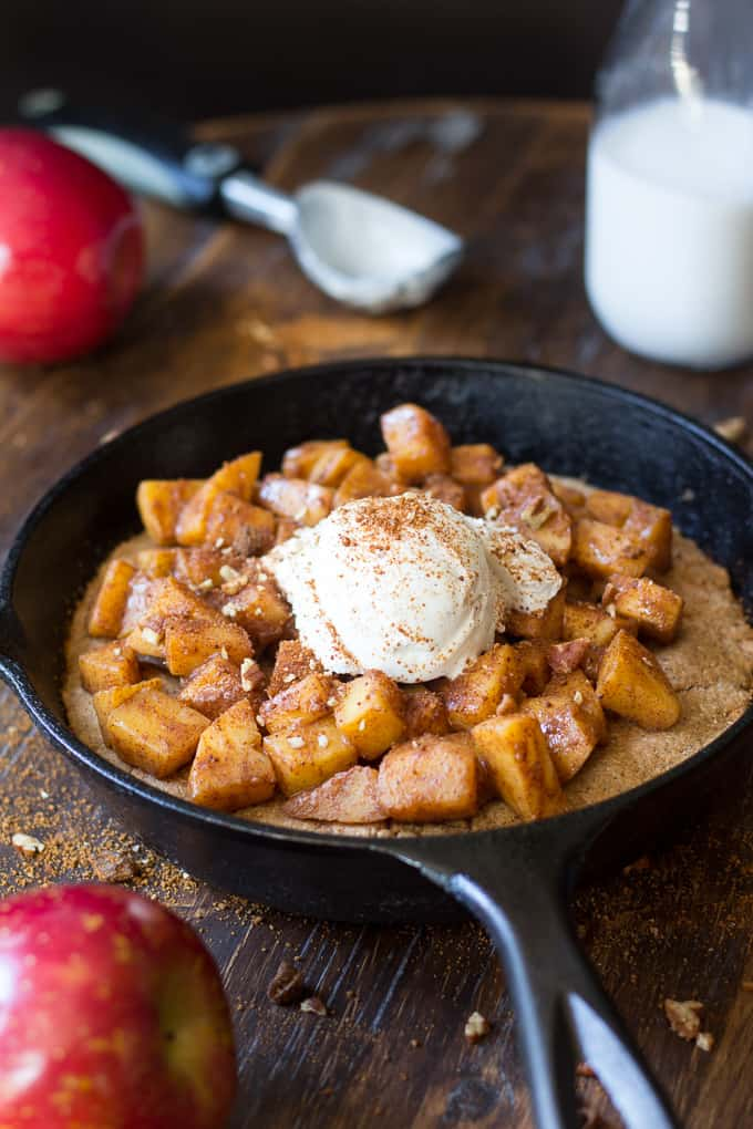 cookie topped with cooked apples and ice cream in a cast iron skillet