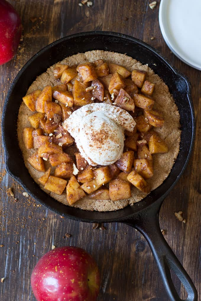 overhead shot of a cast iron skillet with a cookie base topped with cinnamon apples and ice cream