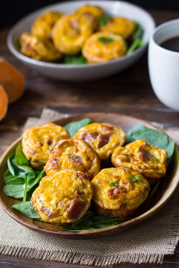 six bacon egg muffins on a bed of spinach in a wooden bowl