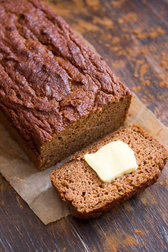 a loaf of pumpkin bread with one piece sliced off with a pat of butter