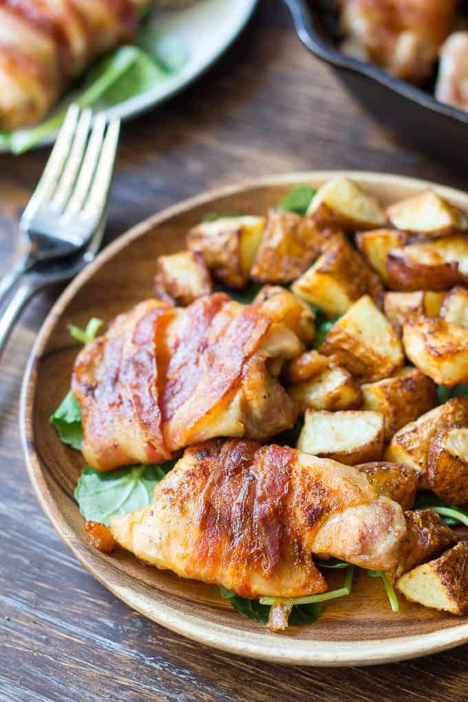bacon wrapped chicken with crispy potatoes over spinach on a wooden plate