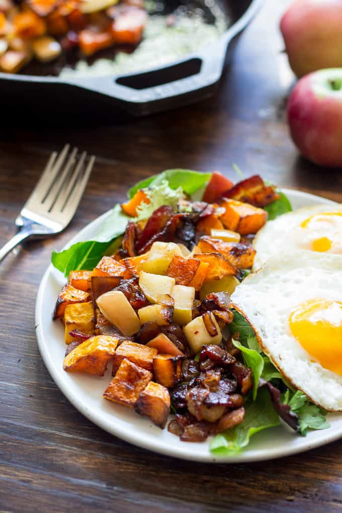 butternut squash hash and two eggs over a bed of greens