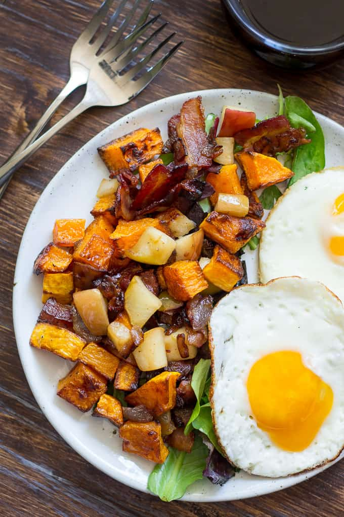 overhead view of squash, apple, and bacon hash with fried eggs & greens on white plate