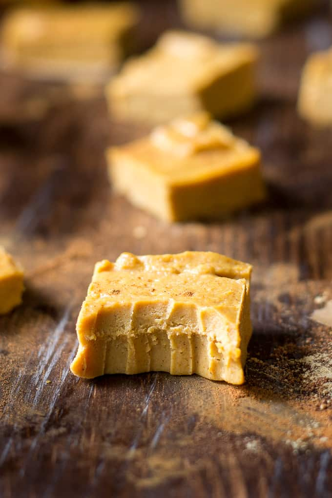 a piece of light orange-brown paleo pumpkin fudge with a bite taken out
