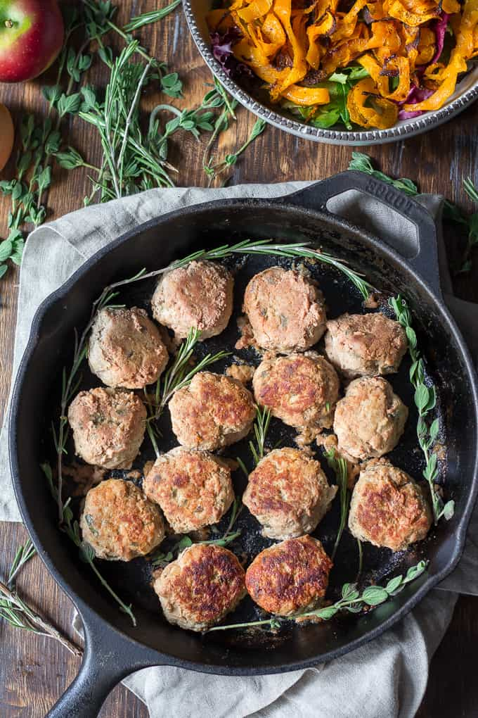 cooked turkey meatballs in a cast iron skillet with fresh herb sprigs