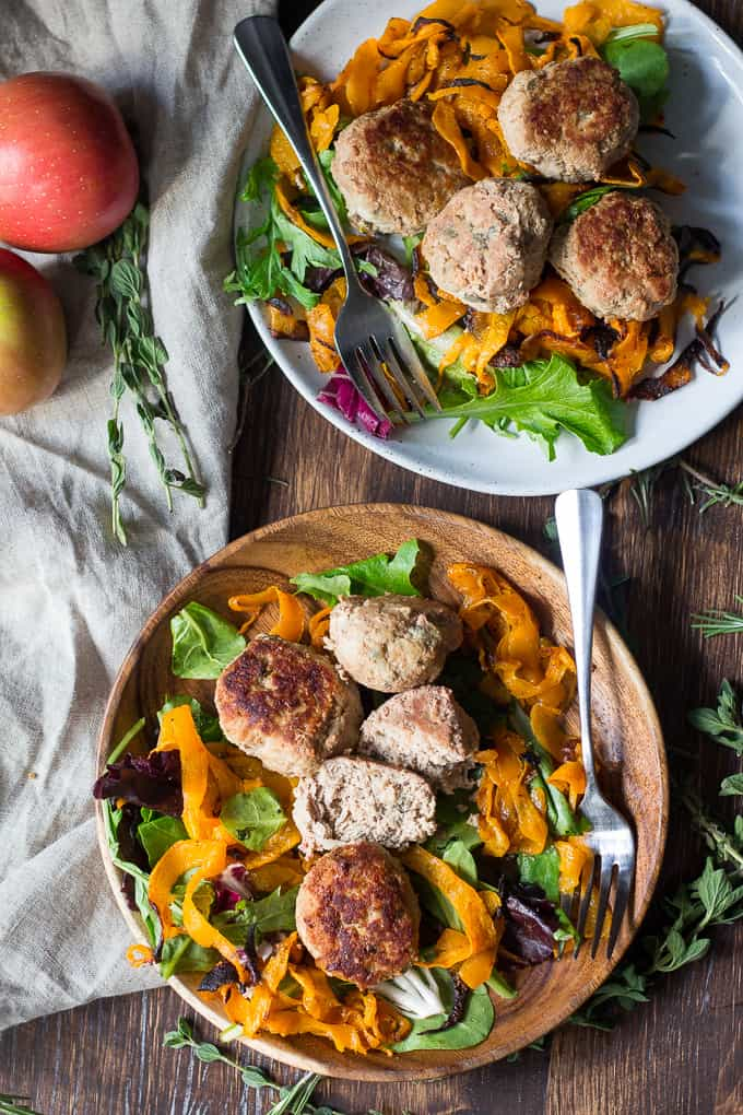 two bowls of meatballs over sweet potatoes and salad with forks