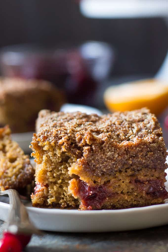 a slice of cranberry orange coffee cake with a bite taken from the edge resting on a white plate