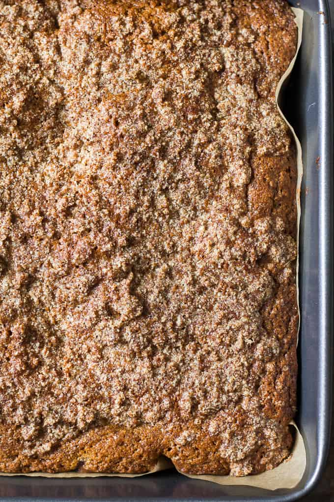 a gray cake pan containing a tan colored cake with streusel topping
