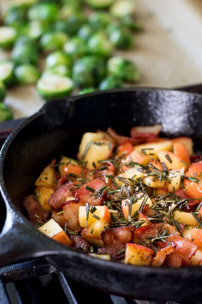 chunks of apples and bacon in a black skillet covered with chopped rosemary