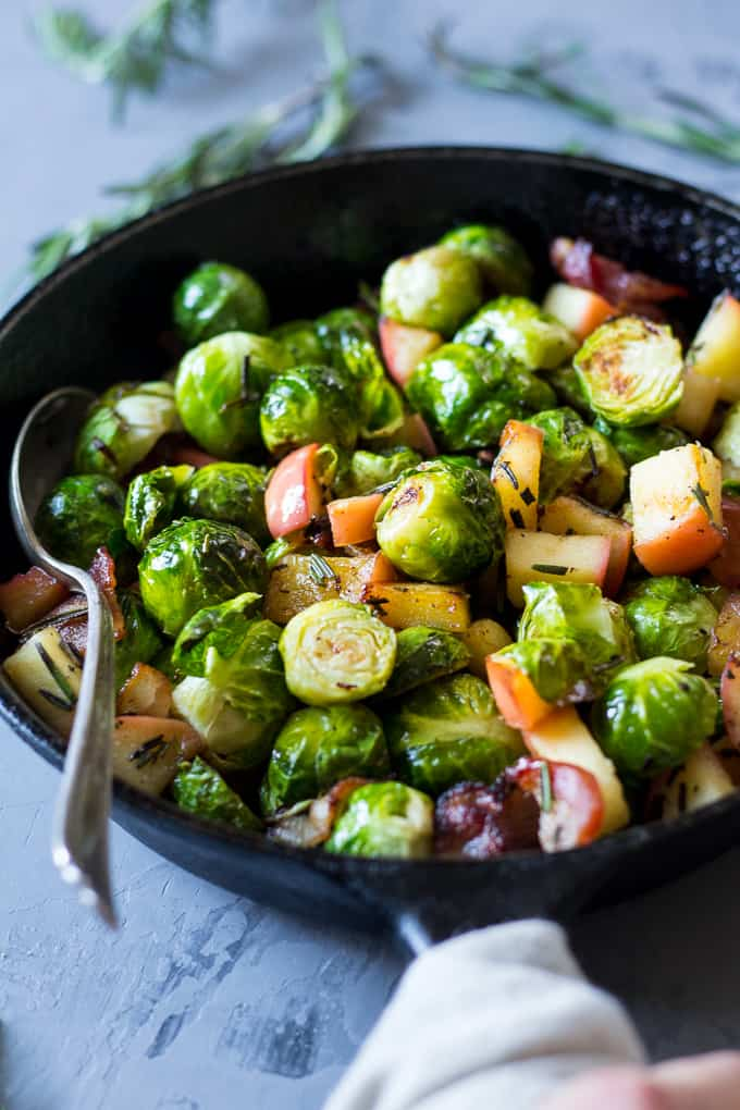 Brussels sprouts with apple and bacon pieces in a black skillet with a spoon