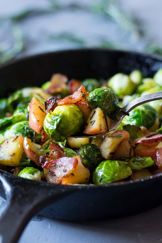 a spoon lifting a scoop of Brussels sprouts with apples, bacon, and rosemary from a cast iron skillet