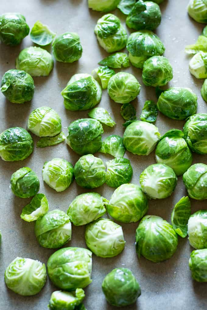 bright green uncooked Brussels sprouts scattered on parchment paper