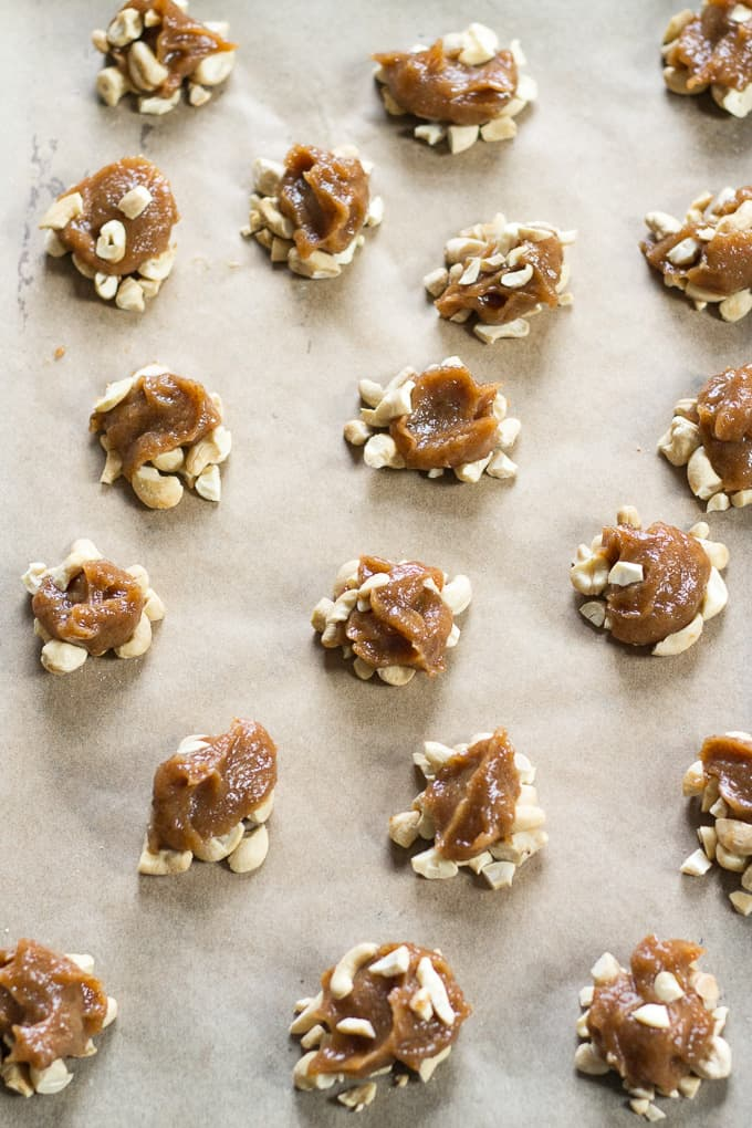 caramel and cashew clusters scattered on a piece of parchment paper
