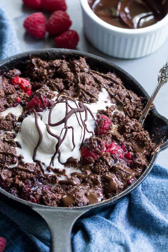 This raspberry chocolate crumble is super easy to make, paleo, vegan, and can be served right out of the skillet!   It's extra tasty topped with melted chocolate and coconut vanilla ice cream.   Gluten free, refined sugar free, dairy free.