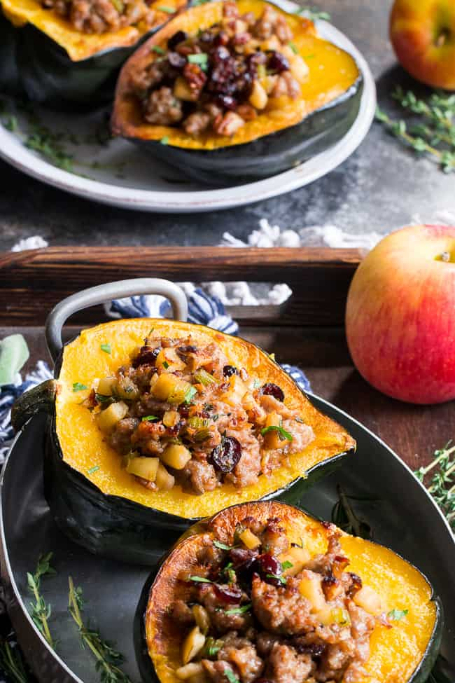 This Roasted Stuffed Acorn Squash is filled with all your favorites - sausage, apples, cranberries, onions, celery and savory herbs. The stuffing is packed with savory/sweet flavors and the perfect addition to a holiday gathering, or for any meal!  Paleo, gluten free, Whole30 compliant.
