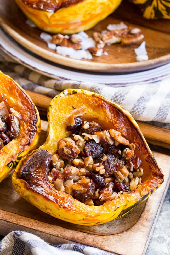 "Winter squash is roasted, filled with a sweet ""candy"" mixture, drizzled with maple and roasted again to combine flavors.  This paleo and vegan roasted squash recipe is perfect as a sweet side dish for the holidays, or a dessert!"