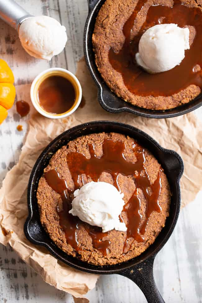This fudgy pumpkin snickerdoodle skillet cookie is loaded with pumpkin spice and cinnamon, drizzled with dairy-free salted caramel sauce and topped with coconut vanilla ice cream.  This rich paleo dessert is perfect for fall and the holiday season!  Kid approved, paleo, dairy-free, grain-free.
