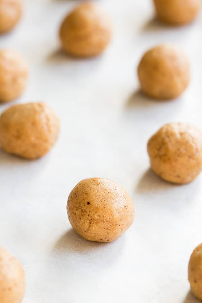 balls of tan colored cookie dough scattered on white parchment paper