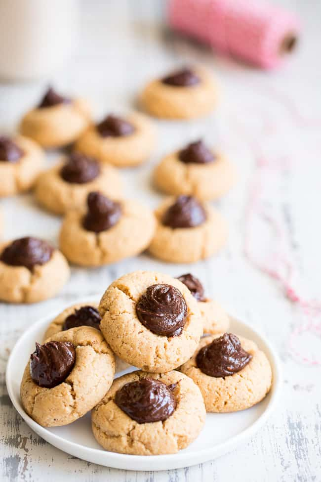 a plate of almond butter cookies with chocolate swirl centers and more cookies in the background