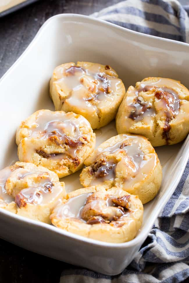 a baking dish with 6 cinnamon rolls drizzled with white icing