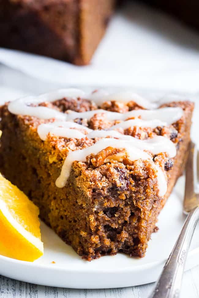 a triangle slice of brown coffee cake with white icing drizzled over top on a white plate with a slice of orange