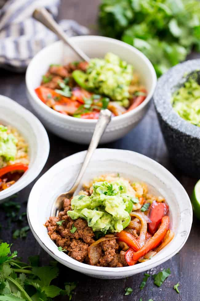 These easy, filling, totally satisfying Paleo Burrito Bowls are packed with spicy seasoned ground beef, sautéed peppers and onions, cauliflower rice and a quick guacamole.  Served over fried cauliflower rice with a kick for maximum flavor!   They're family approved, Whole30 compliant and keto friendly too!