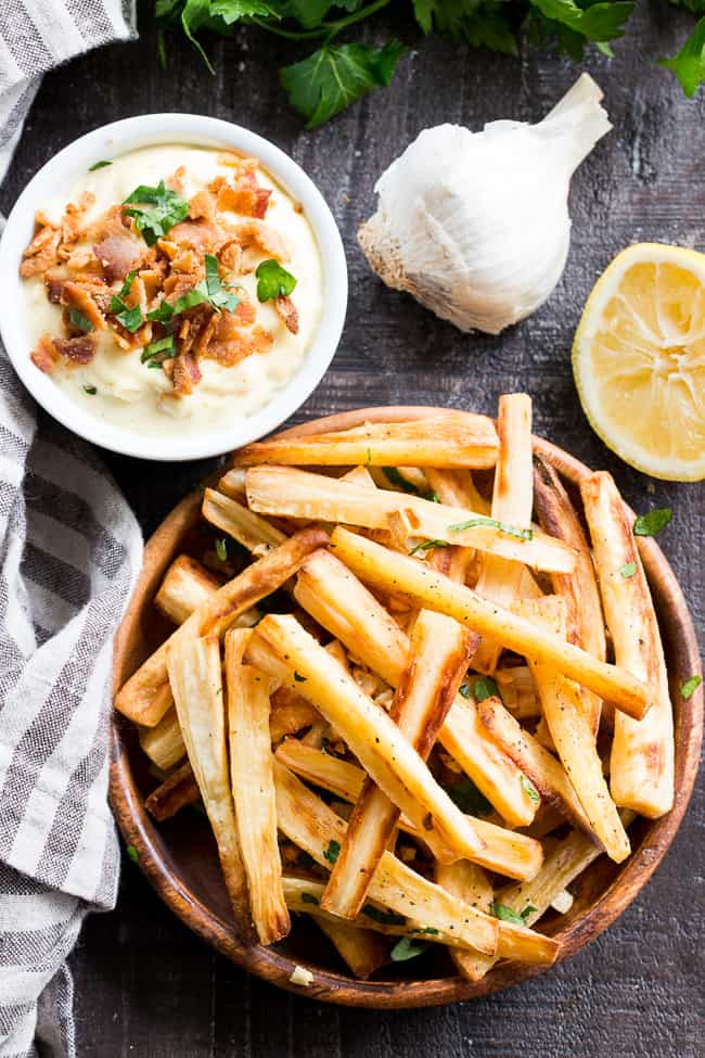 These crispy baked garlic parsnip fries are easy and totally tasty with any main dish!  Lower in carbs than potato fries and packed with flavor, with a creamy, tangy, bacon aioli for dipping.  Kid approved, Paleo and Whole30 compliant, perfect side dish or appetizer.