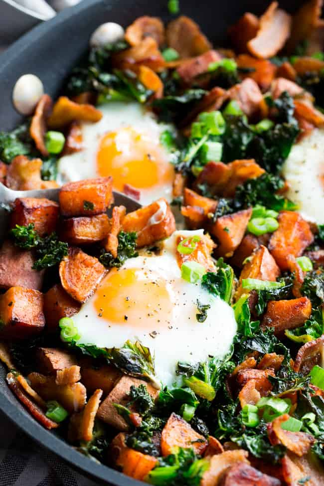 This simple sweet potato hash with kale and bacon is your new paleo and Whole30 go-to breakfast!  Crispy bacon, kale, and sweet potatoes are seasoned and cooked up perfectly in a big skillet, then topped with eggs and garnished with green onion.  It doesn't get easier or more delicious than this hash!