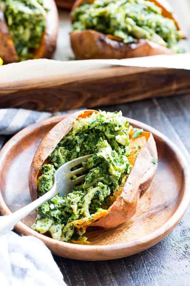 These chicken pesto stuffed sweet potatoes are seriously tasty, filling and easy to make! A paleo and Whole30 compliant pesto is mixed with shredded chicken and tops perfectly baked sweet potatoes.