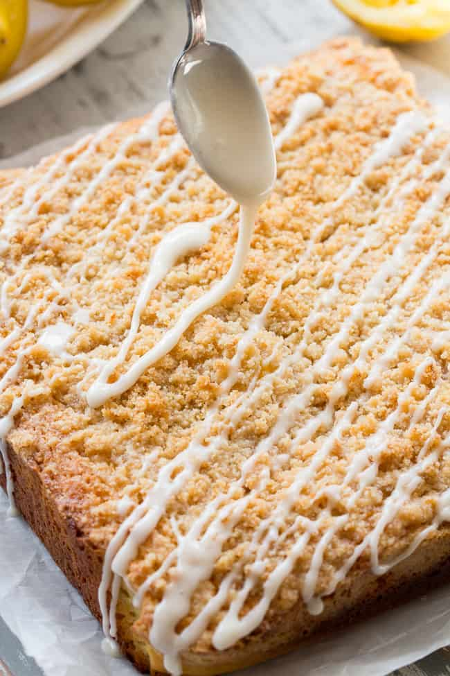 This amazing paleo lemon crumb cake is deliciously sweet/tart and bursting with fresh lemon flavor!  It starts with a  perfectly moist lemon cake layer, topped with lemon curd, piled with crumb topping and drizzled with lemon glaze.  It's gluten-free, dairy-free, paleo will become a favorite dessert with the first bite!