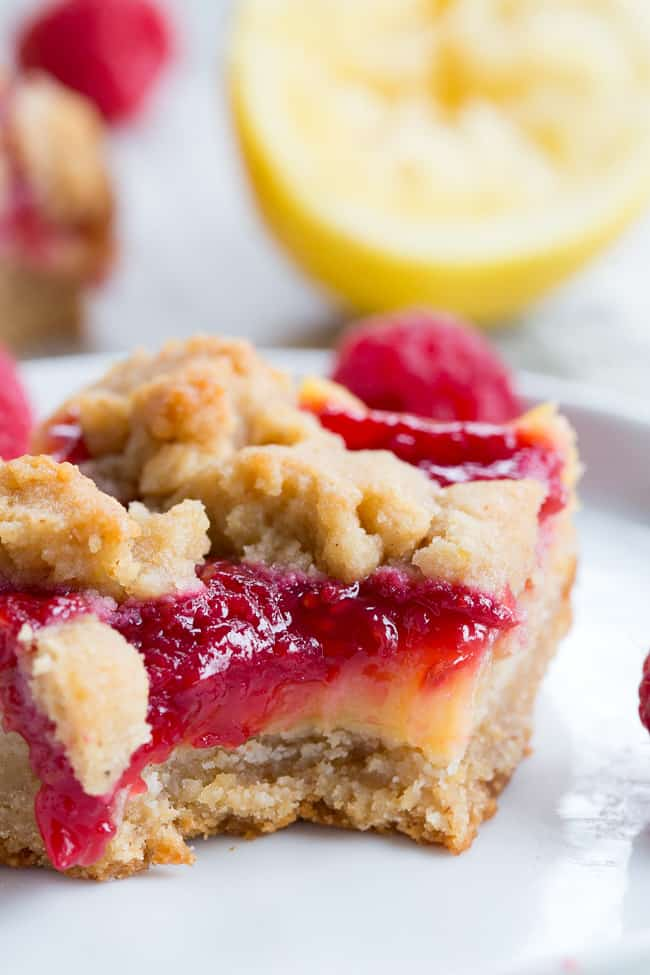 These paleo raspberry lemon bars are absolutely heaven!   A lemon cookie crust is topped with creamy tart sweet lemon curd, homemade raspberry sauce and more cookie crumbles to top.  Everything is baked to perfection and cut into bars for the ultimate dessert!  Gluten-free, dairy-free, no refined sugar, grain free.