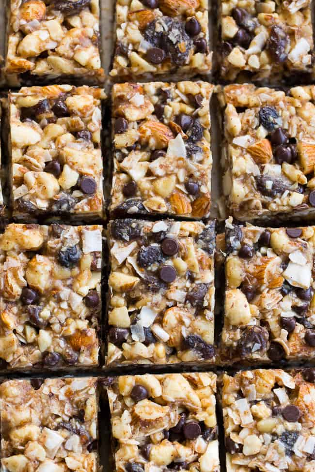 Chewy, crunchy, sweet and salty, these grain free and paleo no bake granola bars are going to become your favorite with the first bite!  They're loaded with raisins and mini chocolate chips, coconut flakes and nuts, sweetened with raw honey and packed with healthy fats.  Kid approved, gluten-free, dairy-free, grain free and addicting!