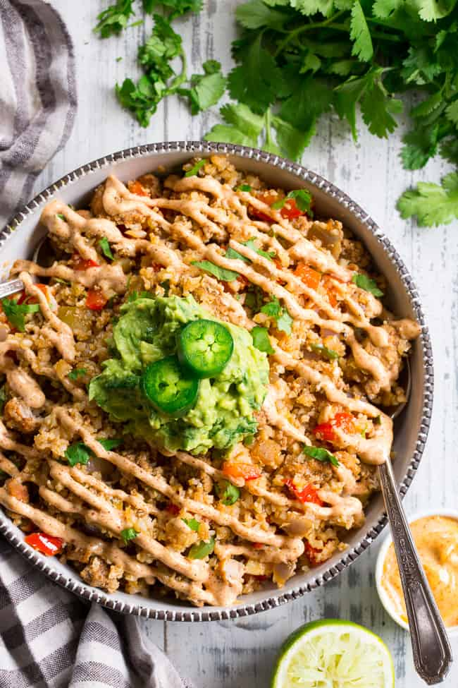 This Mexican Cauliflower Rice is packed with veggies, protein, and lots of flavor and spice!  It's topped with an easy guacamole and chipotle ranch sauce for a tasty, filling meal that's Paleo, Whole30 compliant and keto friendly.