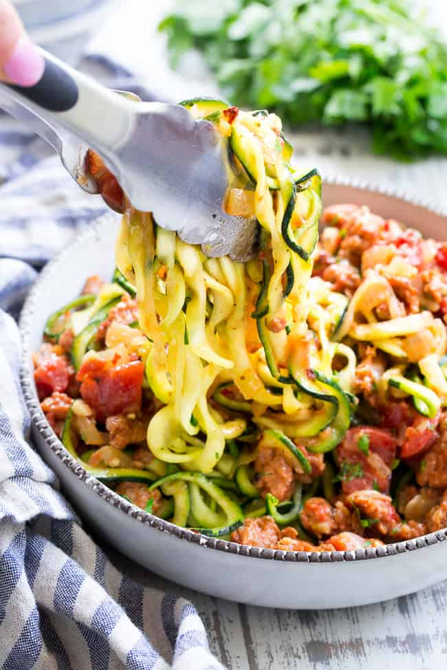 These zucchini noodles are made deliciously savory with lots of spicy Italian sausage, and a creamy tomato sauce.  Quick to throw together on a weeknight and easy to make ahead of time too!  It's a filling, family friendly lunch or dinner that's Paleo, Whole30, dairy free and low carb too!