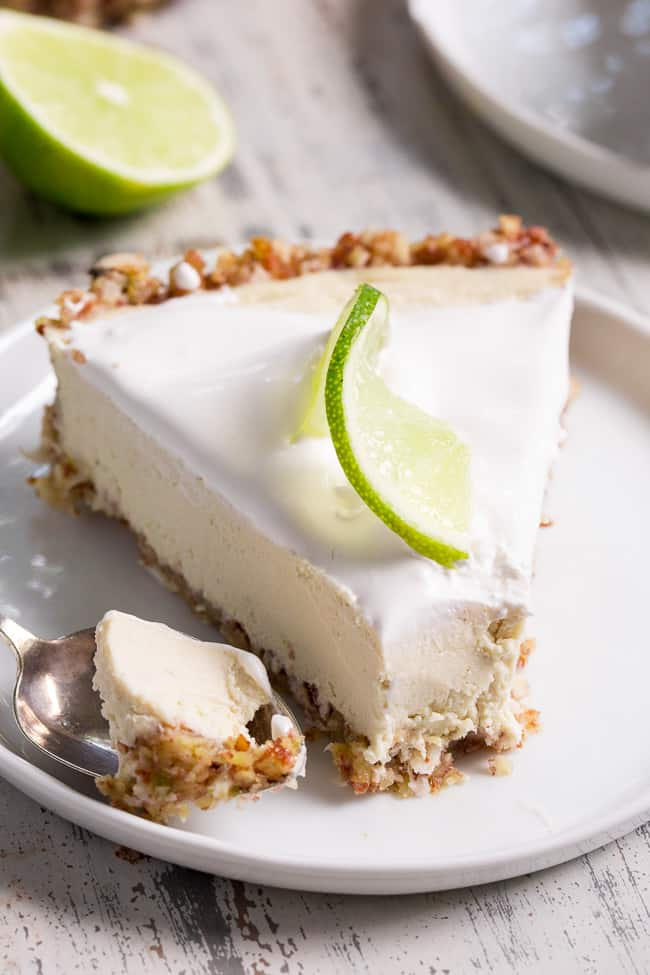 This key lime paleo and vegan cheesecake tart is insanely creamy, perfectly sweet/tart and couldn't be easier to make! The no-bake dairy-free, cashew-based filling blends up quickly and chills to perfection in a simple coconut pecan crust.  It's family approved and sure to become a favorite special occasion dessert!