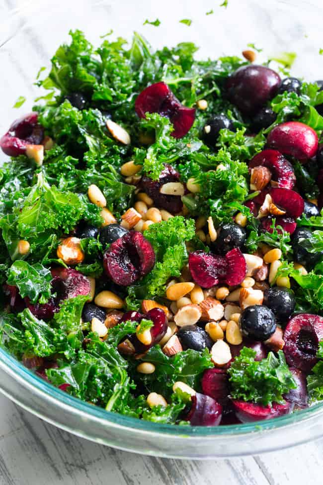 This paleo and vegan kale salad is packed with fresh cherries, blueberries, toasted pine nuts and almonds. It's topped with a simple Whole30 compliant dressing made with fresh berries and cherries too! Perfect as a side salad for summer or top it with your favorite protein for a full meal.