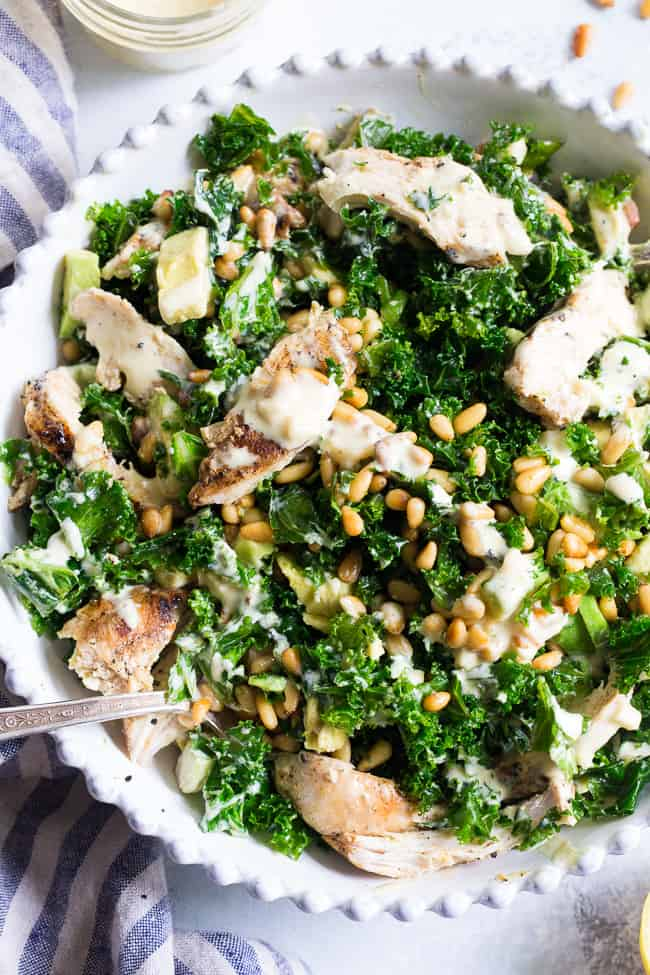 This Paleo and Whole30 Kale Chicken Caesar Salad is an easy, healthy lunch or dinner packed with so much flavor! Grilled chicken is tossed with avocado, toasted pine nuts, chopped kale, and a creamy homemade dairy-free caesar dressing for a deliciously savory salad that you'll want to make again and again.
