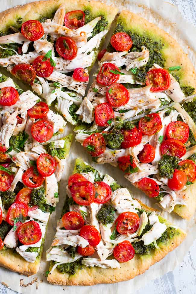 This simple chicken pesto pizza starts with the perfect quick and easy paleo pizza crust, topped with a flavor-packed dairy-free homemade pesto, shredded chicken and cherry tomatoes.  This fun meal great for dinner or lunch, is kid approved, grain-free, dairy-free and insanely delicious.