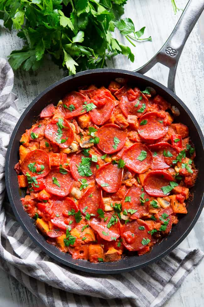 This sweet potato skillet is loaded up with all your favorite goodies just like a pepperoni pizza!  Pan-fried sweet potatoes with peppers, onions, mushrooms, pepperoni and pizza sauce make this paleo, gluten-free, dairy-free skillet quick, easy, and absolutely delicious!
