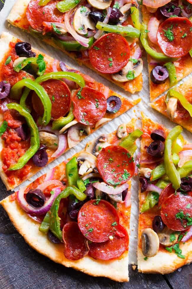 This paleo pepperoni pizza is loaded with all your favorite veggies and packed with flavor!  It's baked on the perfect paleo pizza crust and is totally dairy free, gluten free, grain free and soy free.  This healthy pizza is family approved and easy to make, too!
