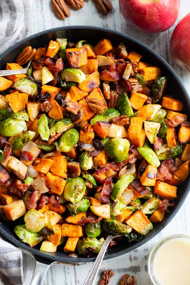 This harvest hash is everything you're craving for the fall season, or anytime!  It's loaded with roasted veggies, apples, bacon, pecans and raisins for a sweet, savory and healthy dish!  The apple vinaigrette add the perfect final touch!  Paleo, Whole30 compliant and great for any meal or as a holiday side dish!