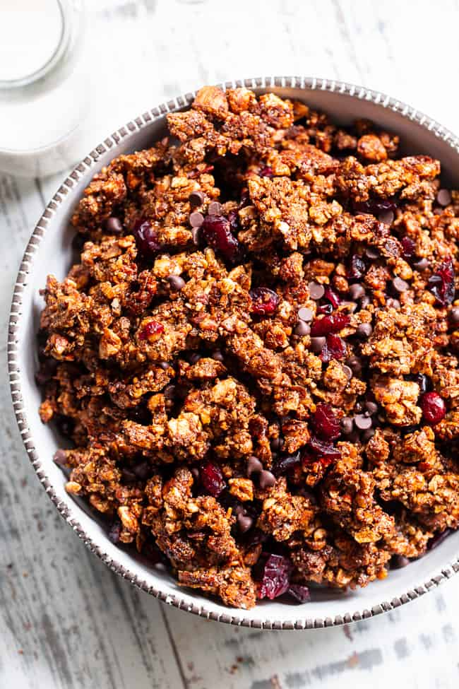 This Paleo gingerbread granola is perfect for snacking or breakfast! The crunchy granola clusters are sweetened with maple and molasses, baked until toasty, and mixed with sweet cranberries and dark chocolate chips. Vegan, grain free, dairy free.