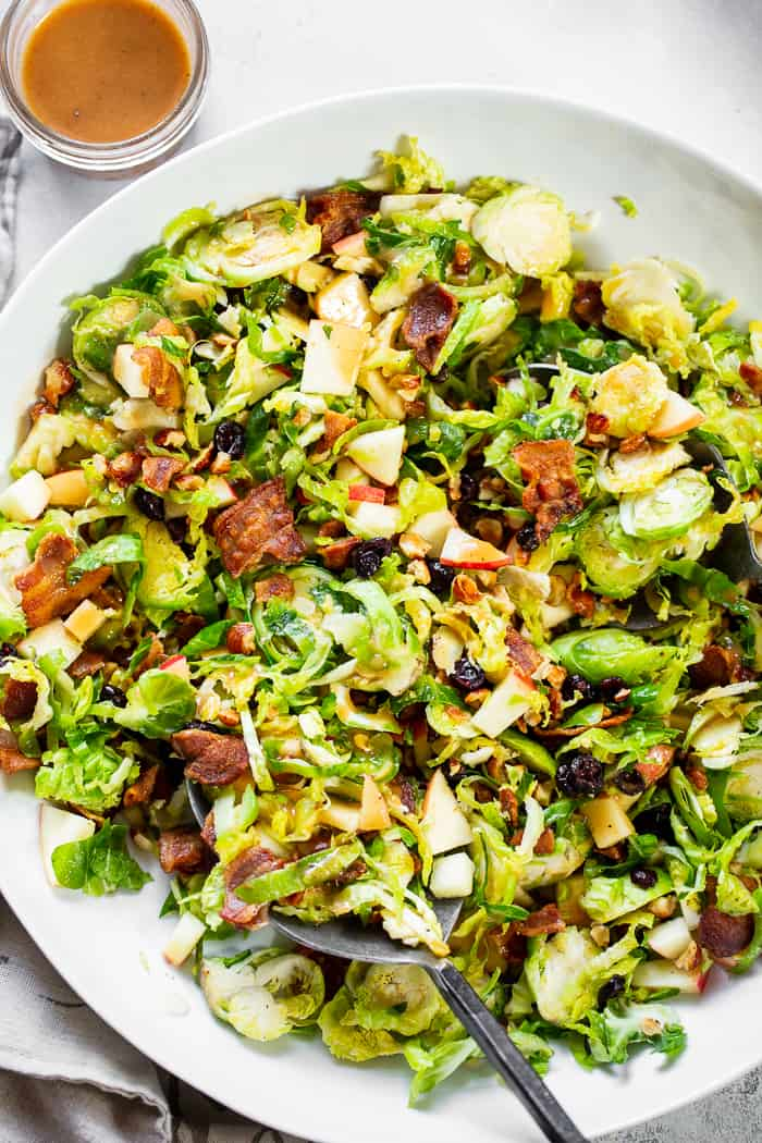 This shredded Brussels sprouts salad is loaded with so many delicious things!  Sweet chopped apples, crispy bacon, toasted hazelnuts and a sweet tangy apple vinaigrette.  It's paleo, dairy-free, with a Whole30 option and perfect for a crowd or as a make ahead lunch.